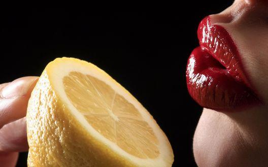 Обои Девушка держит у губ половину лимона