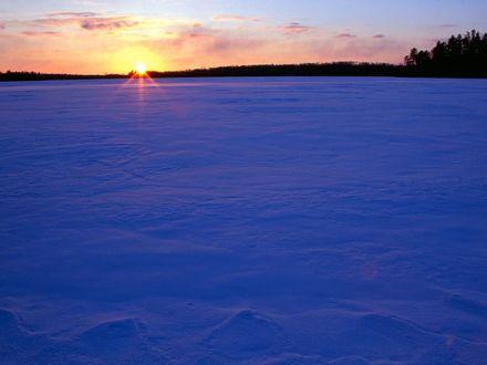Обои Замерзшее озеро и занесенное снегом на фоне закатного неба