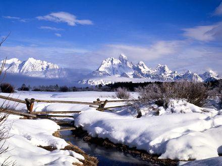 Обои Мостик проходящий через не замерзший ручеек на фоне заснеженных гор
