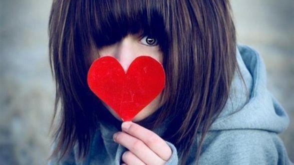Обои Девушка прикрыла лицо сердечком