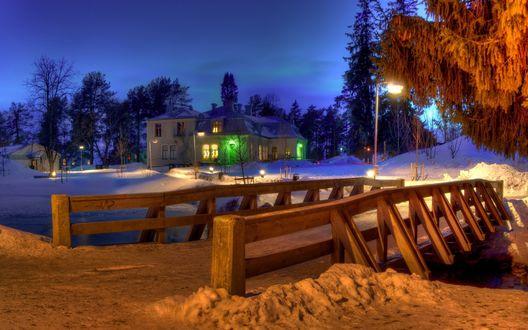 Обои Деревянный мостик, проложенный через неширокий, незамерзающий ручей с проходящей по нему заснеженной дорогой, ведущей к окраине поселка, освещенной стоящими по обочинам электрическими фонарями на фоне вечернего синего неба