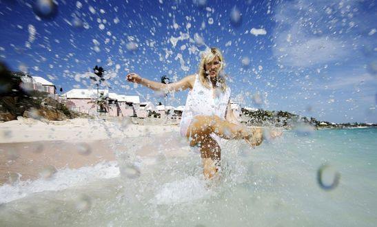 Обои Радостная девушка стоит в море и ногой разбрызгивает воду