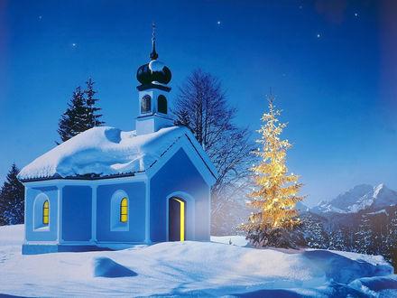 Обои Не большая церквушка стоит на заснеженной горе рядом новогодняя елка с горящими гирляндами