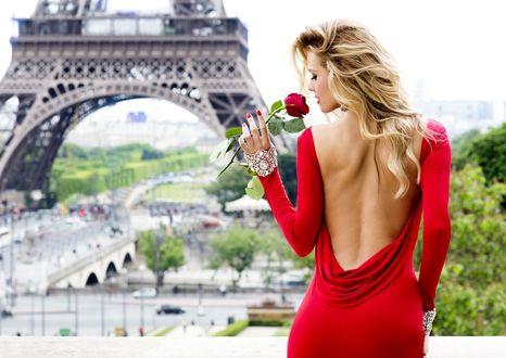 Обои Девушка, в красном платье от Tarik Ediz, с оголенной спиной, держит розу в руке, она стоит на фоне города Париж с Эйфелевой башней / Paris la tour Eiffel