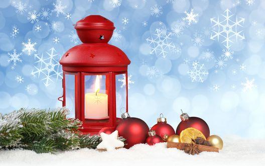 Обои Фонарь, с горящей внутри свечой, стоит в снегу, рядом лежат еловые ветки, елочные шары, долька лимона и корица
