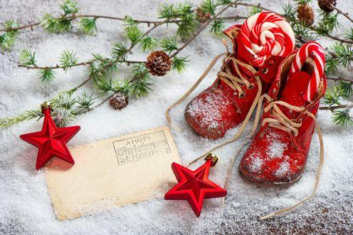 Обои Красные ботинки, с новогодними сладостями внутри, стоят на снегу, рядом лежит письмо, еловые ветки и две елочных игрушки