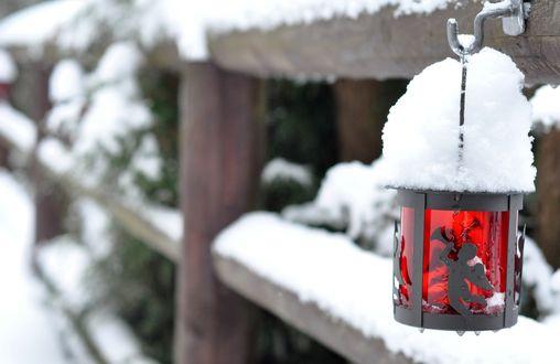 Обои Фонарь, покрытый снегом, висит на деревянном заборе