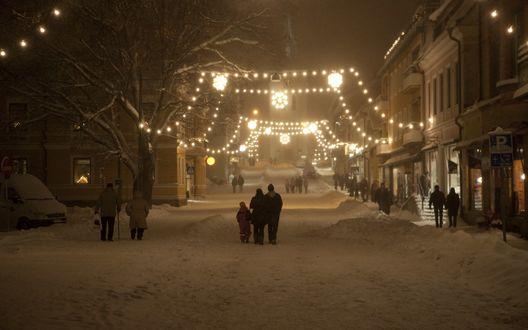 Обои Люди идут по зимней улице, освещаемой фонарями