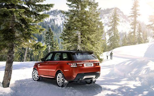 Обои Парень с девушкой оставили оранжевый Range Rover под елями, а сами пошли кататься на лыжах в заснеженном лесу