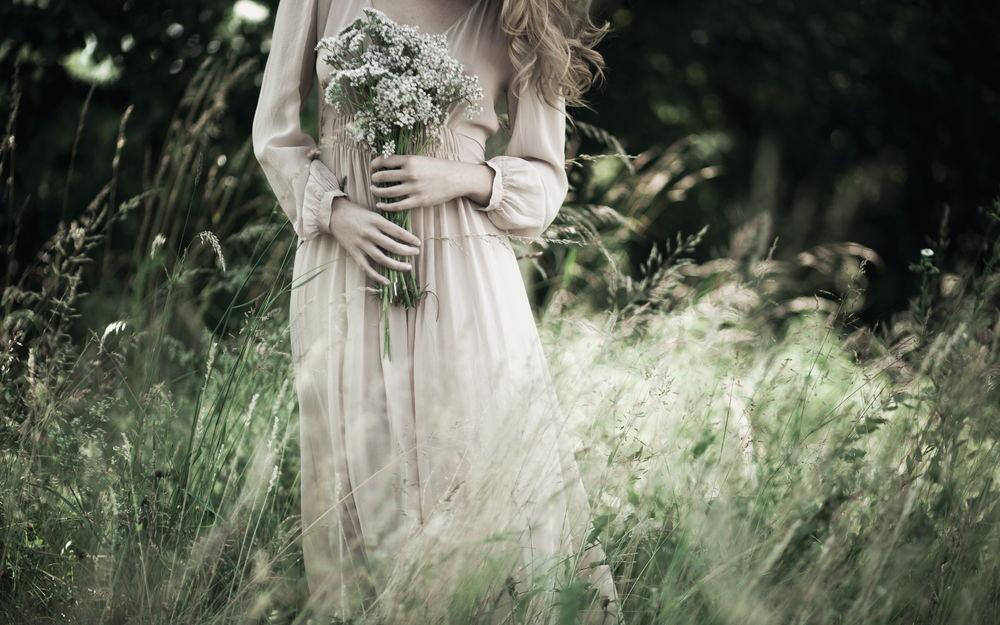 Обои для рабочего стола Девушка в длинном светлом платье стоит с букетом цветов в поле