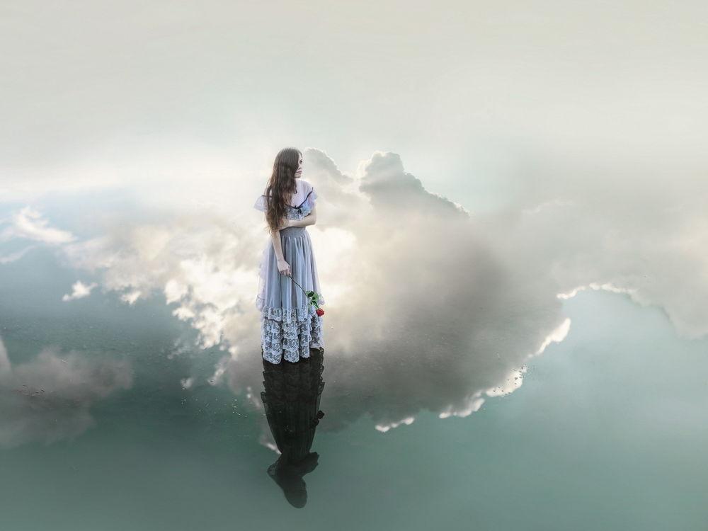Обои для рабочего стола Девушка в длинном платье, с розой в руке, стоит на воде, где отражается сама и отражаются облака