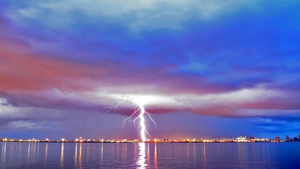 Обои Сноп молний раскалывает пополам небо и прицельно бьет по городу на берегу реки