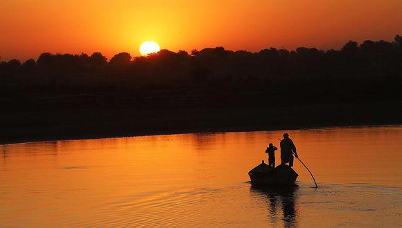 Обои Дедушка с внуком, стоящие на двух, рядом плывущих лодках на фоне заходящего за вершины деревьев солнца, осветившего своими багряными лучами водную поверхность реки