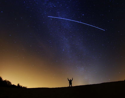 Обои Мужчина, стоящий на поляне рядом с растущими деревьями, подняв руки вверх, любуется ночным звездным небом с падающей кометой, оставляющей за собой яркую световую линию