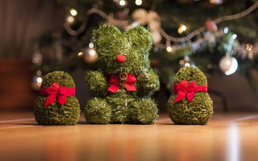 Обои Зеленый мишка и два снеговика сидят на полу на фоне новогодней елки