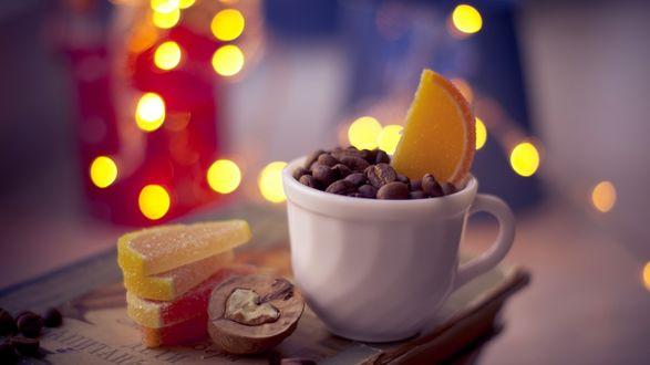 Обои В белой кружке насыпаны зерна кофе и лежит конфетная лимонная долька, рядом лежат также такие же дольки и конфетный орех с сердечком внутри