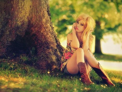 Обои Девушка с фотоаппаратом сидит в траве, облокотившись на ствол ...