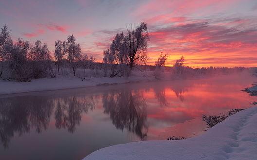 Обои Багряный закат на небосклоне с перистыми облаками отразился в незамерзающей поверхности реки с заснеженными берегами, с легким туманом, поднимающимся с поверхности воды