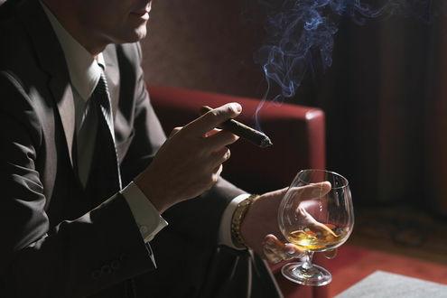 Обои Мужчина в костюме сидит на кресле с сигарой и бокалом с напитком в руках