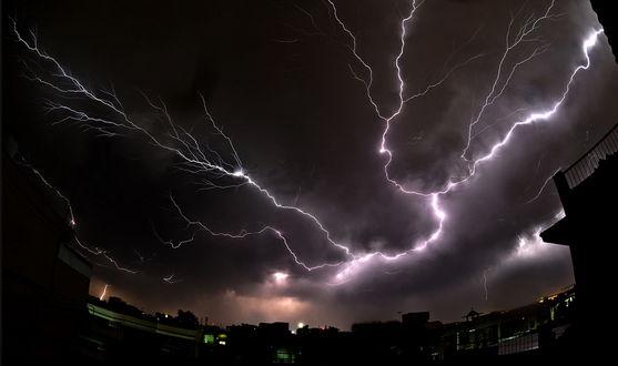 Обои Сверкающие многочисленные разряды молний в ночном небе над городской окраиной