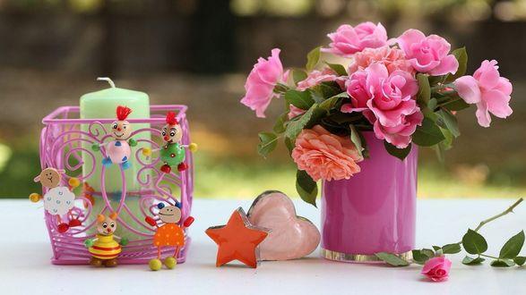 Обои Розы в вазе и роза на столе, рядом игрушки в виде сердечка, звезды и подставка со свечой внутри, на которой висят игрушечные человечки и животные
