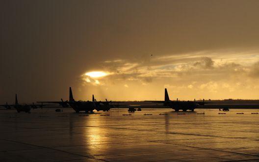 Обои Военно-транспортные самолеты Российских ВВС Ан-12, стоящие на стоянке военного аэродрома на фоне заката, Россия / Russia