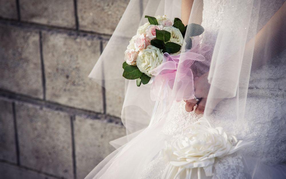 Обои для рабочего стола Девушка в свадебном платье с букетом роз в руках