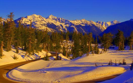 Обои Извилистая асфальтированная дорога с заснеженными обочинами, растущими на них деревьями на фоне красивого горного ландшафта и яркого синего голубого, безоблачного неба