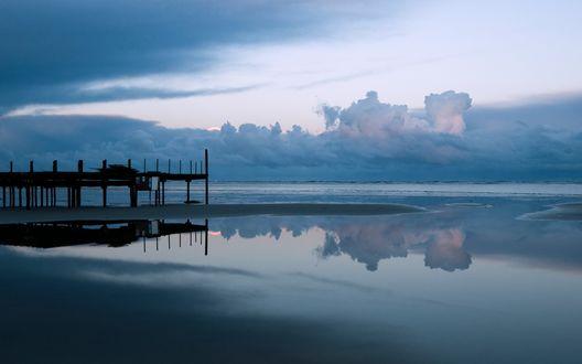 Обои Небольшой мост на берегу моря, в котором отражаются облака
