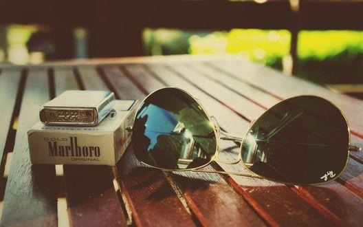 Обои Пачка сигарет Marlboro / Мальборо, зажигалки и солнечные очки на деревянной поверхности