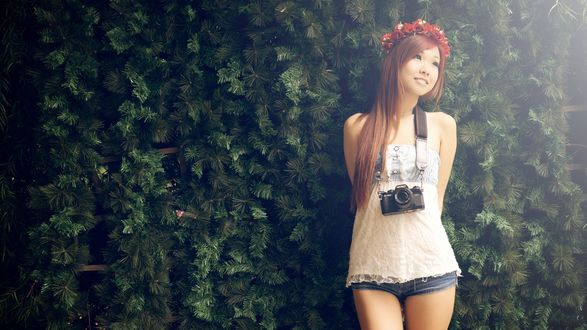 Обои Девушка азиатка с фотоаппаратом на груди на фоне искуственных елок