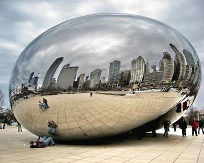 Обои Зеркальный шар в котором отражаются дома города и люди