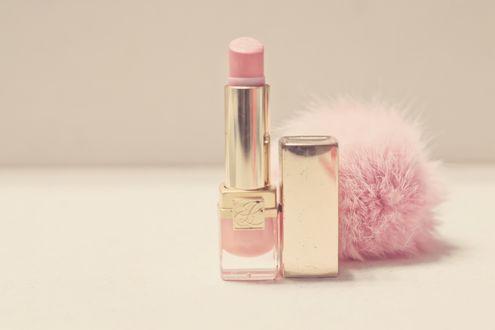 Обои Губная помада нежно-розового цвета стоит на ровной поверхности