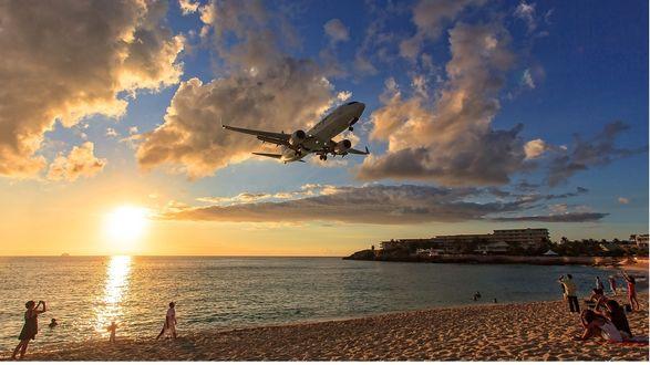 Обои Самолет в небе, пролетающий над пляжем, где отдыхают люди