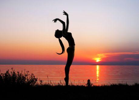 Обои Девушка на цыпочках стоит с поднятыми руками на фоне заката, фотограф Luna Messi