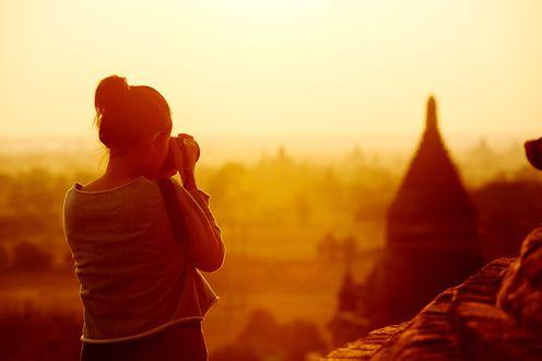 Обои Девушка фотографирует город на закате дня