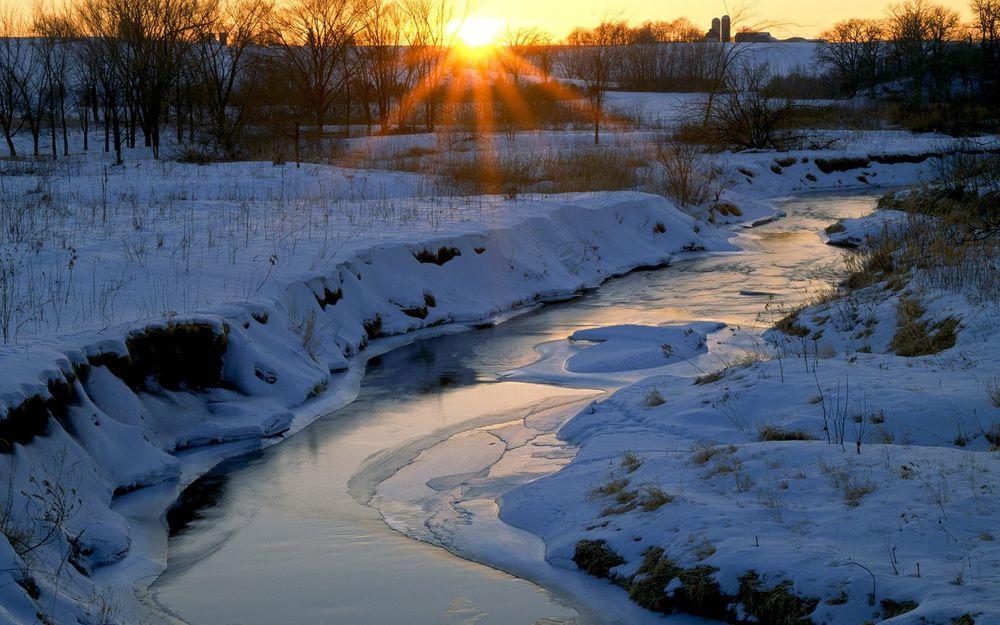 Обои для рабочего стола Восходящее из-за линии горизонта солнце осветило своими лучами замерзший ручей, протекающий среди заснеженных берегов