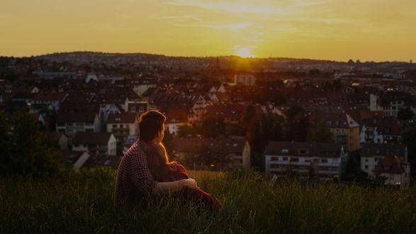 Обои Влюбленные сидят в обнимку на зеленом холме смотря на город во время заката