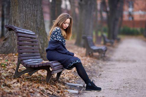 Обои Грустная девушка сидит на краешке осенней скамьи в парке