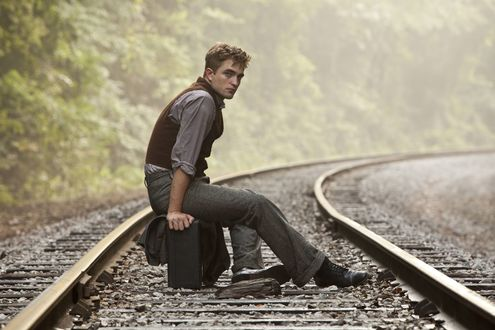 Обои Актер Роберт Паттинсон / Robert Pattinson сидит на чемодане на рельсах, ожидая поезда