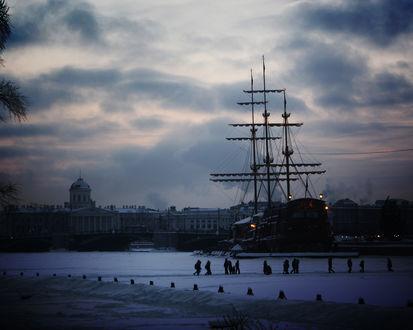 Обои Огромный корабль стоит в снегах в вечернем Санкт-Петербурге, мимо проходят люди