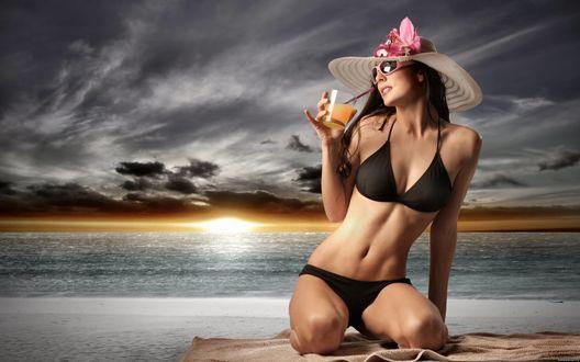 Обои Девушка с коктейлем сидит на пляже в шляпе с цветком