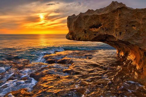 Обои Восходящее солнце на утреннем небосклоне с разноцветными облаками осветило золотистыми лучами скалистое, морское побережье