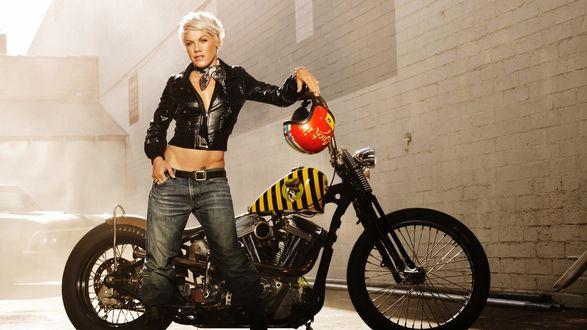 Обои Певица Пинк / Pink рядом с мотоциклом, на котором висит красный шлем