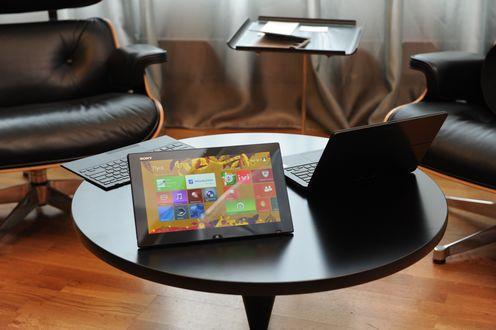Обои Планшет фирмы Sony / Сони на столе, с установленным программным обеспечением Windows / Виндоус, рядом стоит ноутбук