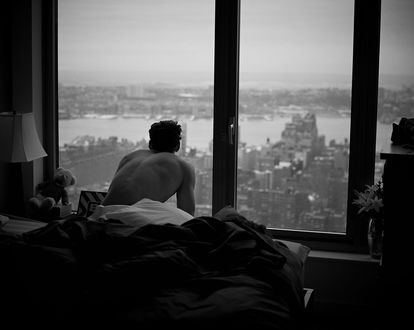 Обои Дэвид Ганди / David Gandy сидит на кровати в полу-темной комнате и смотрит на город через панораманое окно