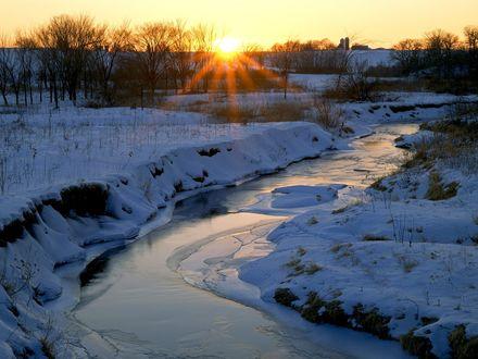 Обои Покрывшаяся льдом узкая река течет посреди поля