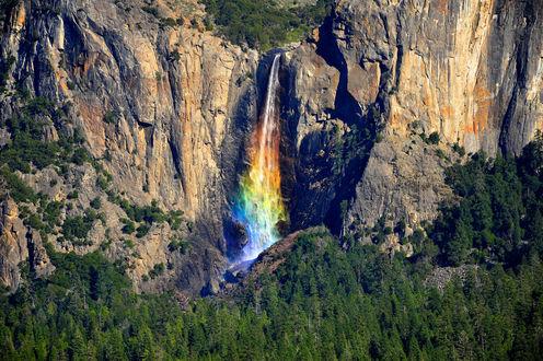 Обои Вид на гранитные скалы и радужный водопад среди скал в Yosemite National Park / Национальном парке Йосемити в California / Калифорнии, на фоне растущих внизу под скалами деревьев