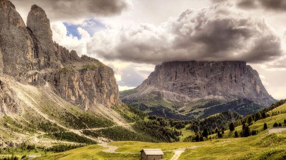 Обои Домик в долине среди гор, над которыми нависли свинцовые тучи