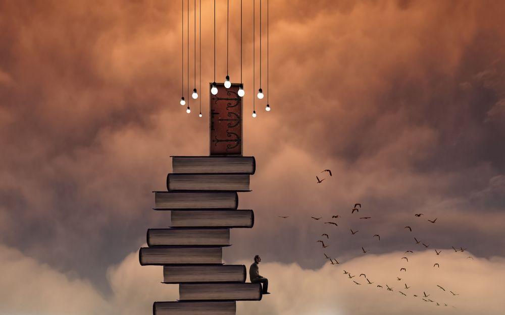 Обои для рабочего стола Мужчина сидит на стопке книг, над которой нависают лампочки, глядя на пролетающую рядом стаю птиц